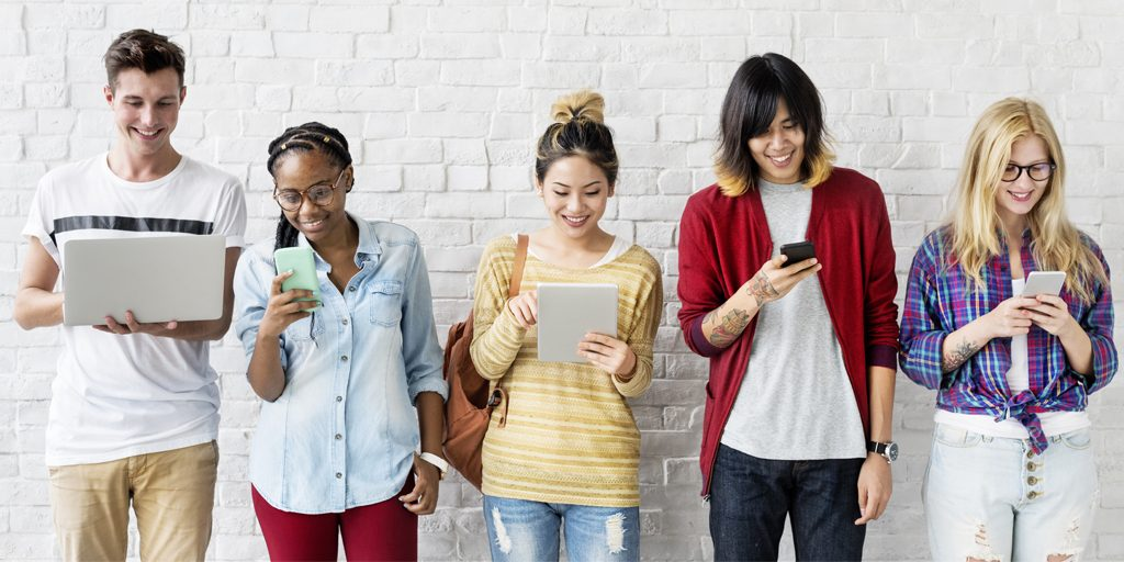 diverse young people smiling at electronic devices
